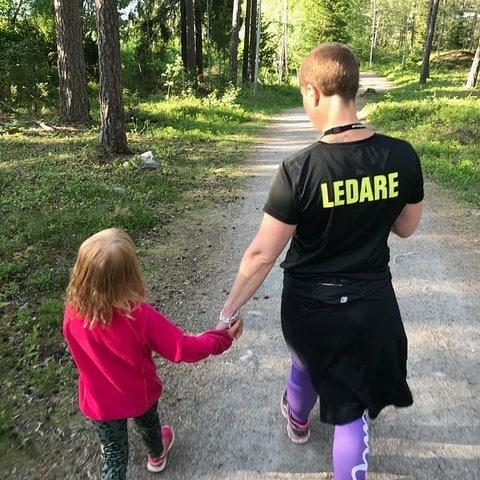En av våra ledare följer en ung deltagare hand i hand i löpspåret
