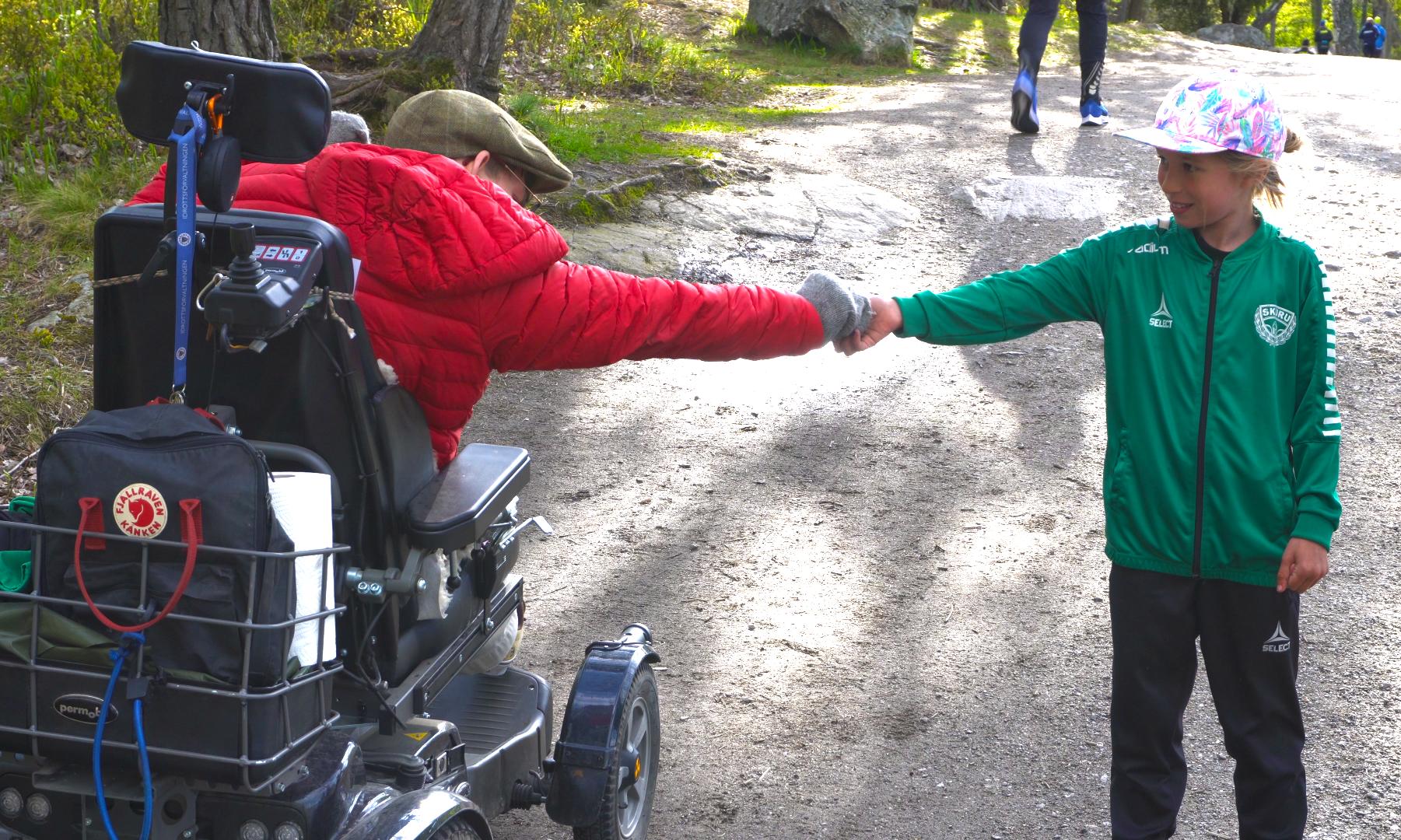 Träningsledaren Adam skakar hand med en ung deltagare. Han sitter i en permobil och har på sig en röd jacka och gråa vantar.