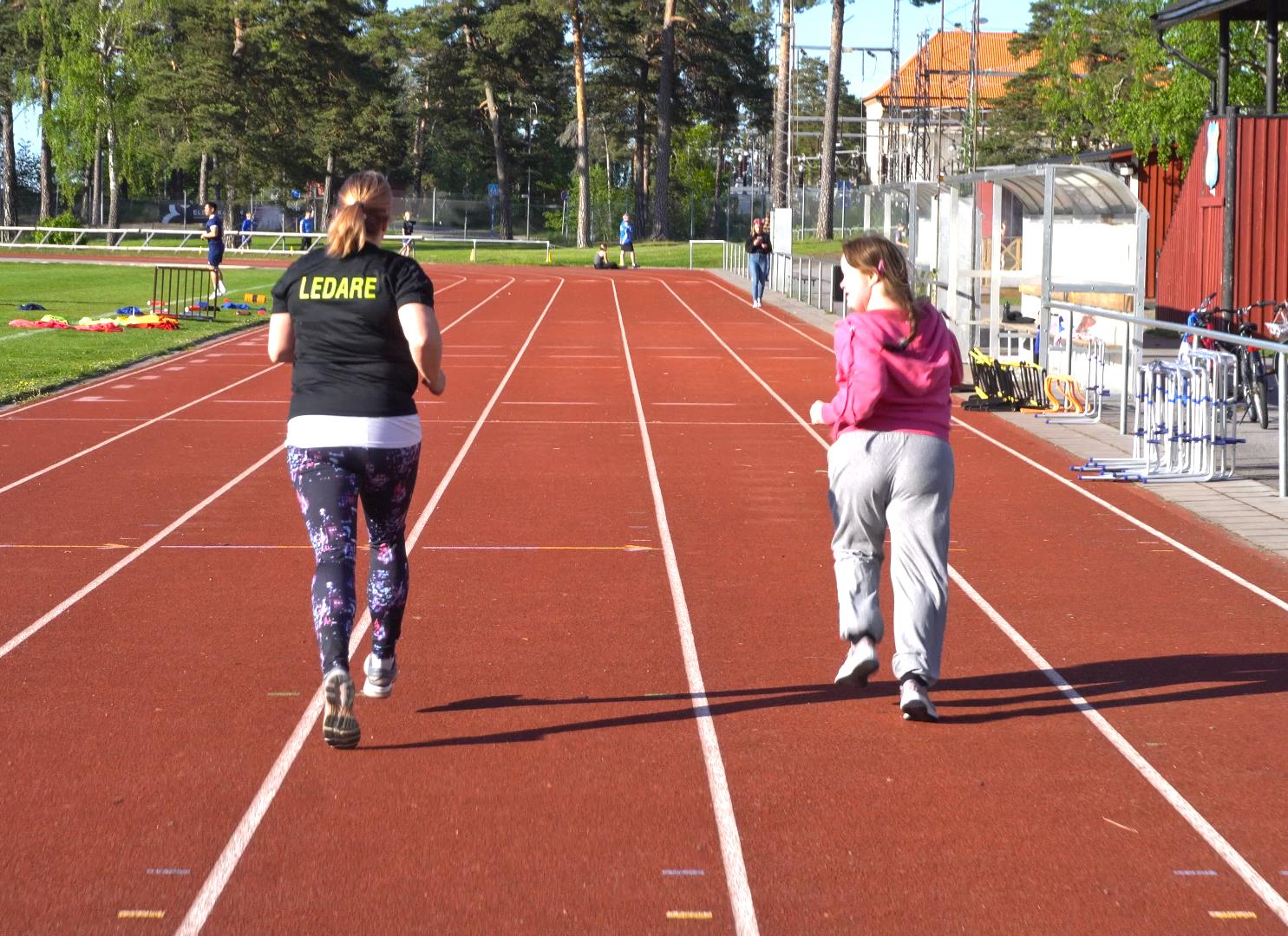 En ledare springer bredvid en deltagare på en löparbana.